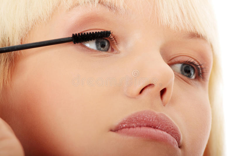 Close up on beautiful young woman doing make up on eyelashes. stock photo