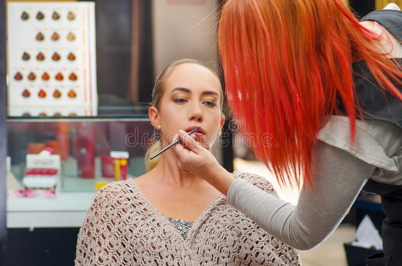 Close up of beautiful young woman getting make-up. The artist is applying lipstick on her mouth, in a blurred background.  royalty free stock photos
