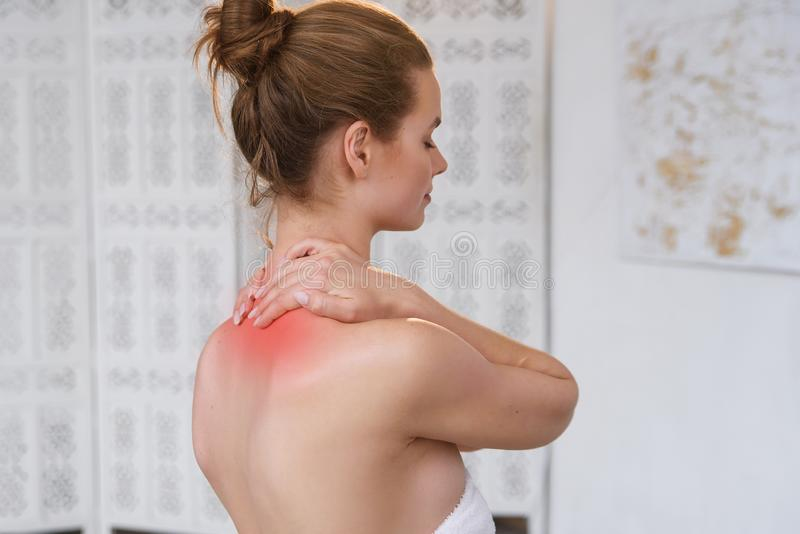 Beautiful young woman has neck pain. Female suffering from painful feeling in muscles, holding hands on her neck. Health royalty free stock photos