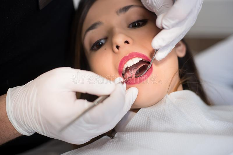 Close up of beautiful young woman having dental check up in dental office. Dentist examining a patient`s teeth with dental tools - mirror and probe. Dentistry stock photo