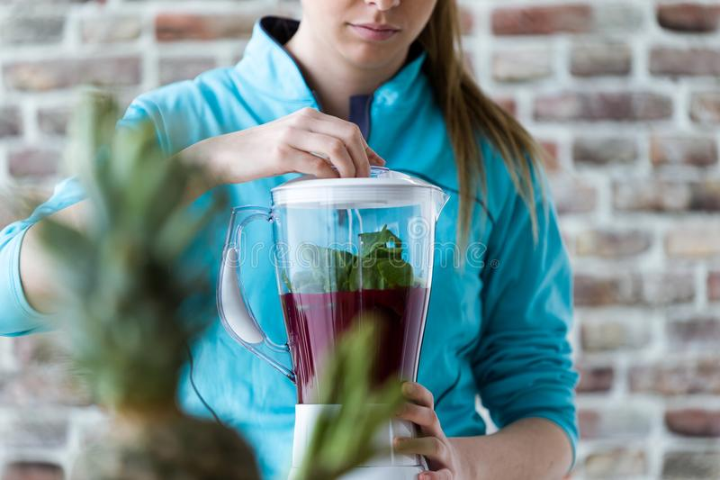 Beautiful young woman preparing detox juice in the blender at home. stock images