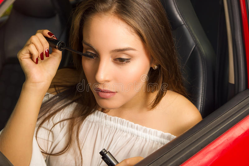 Close up of a beautiful young woman in red car using an eye mascara.  stock images