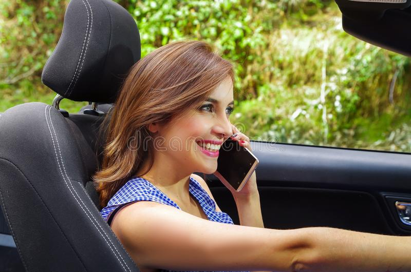 Close up of beautiful young woman using her cellphone inside of the black car, while driving her car with one hand, in a stock images