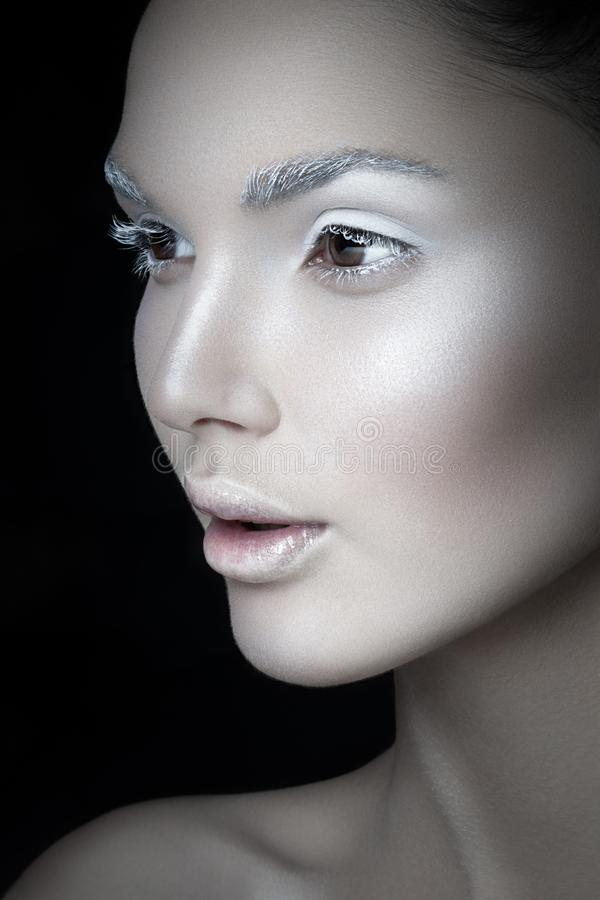 Close up profile portrait of a young woman, with artistic makeup,  on a black backgorund. Creative concept. stock image