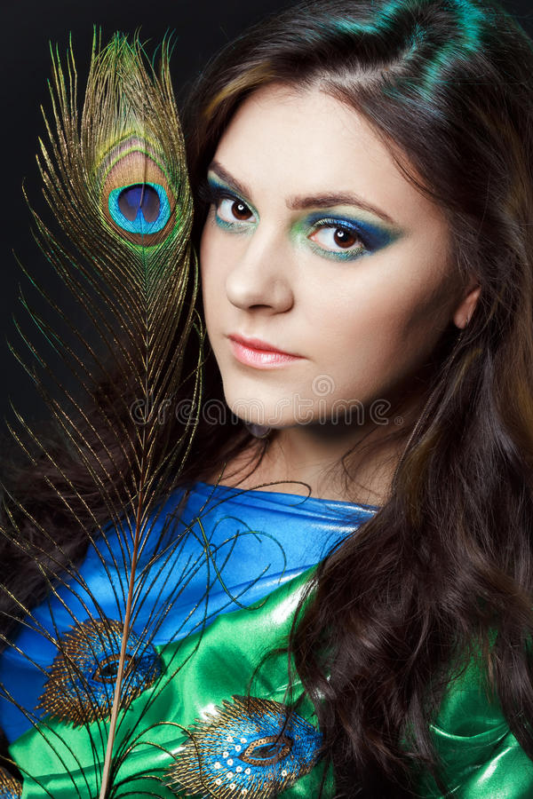 Close up beauty portrait of beautiful girl with peacock feather. Creative makeup peafowl feathers. Attractive mysterious. Beauty portrait of beautiful girl stock photo