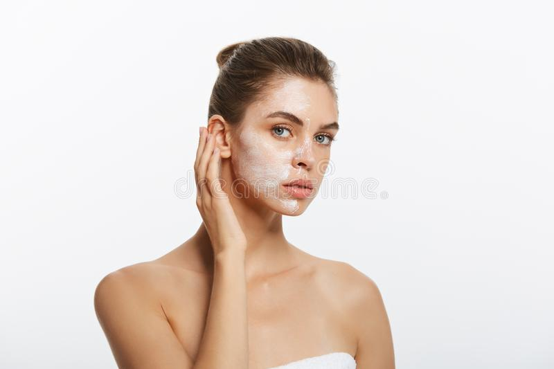 Close up beauty portrait of beautiful half naked woman applying face cream. Isolated over white background stock photo