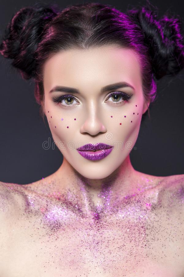Close up beauty portrait of a fantasy art theme: Star Wars cosplay. Princess Leia hairstyle with purple glitters and stars all royalty free stock photo