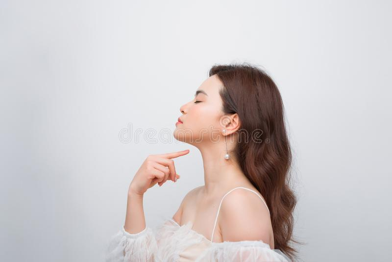 Close up beauty portrait of a smiling attractive woman cleaning her face with a cotton pad  over white background royalty free stock images