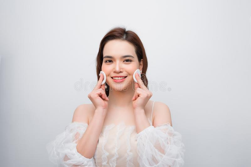 Close up beauty portrait of a smiling attractive woman cleaning her face with a cotton pad  over white background royalty free stock image