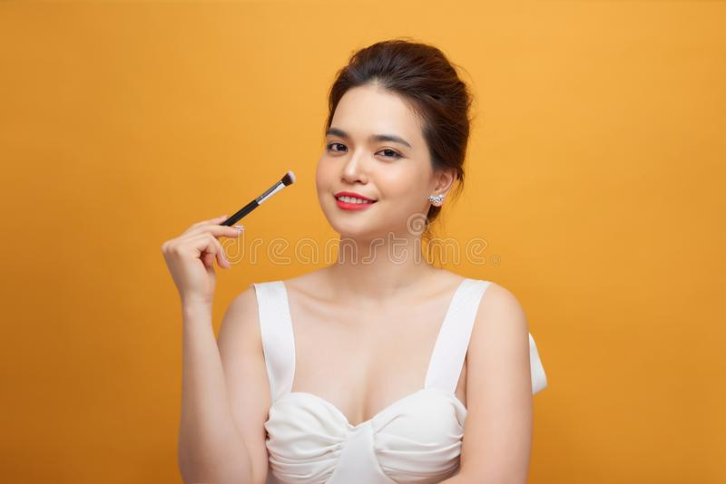 Close up beauty portrait of a smiling attractive woman cleaning her face with a cotton pad  over white background stock image