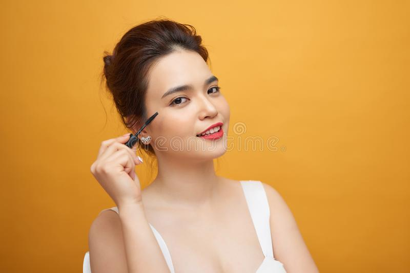 Close up beauty portrait of a smiling attractive woman cleaning her face with a cotton pad  over white background stock photos