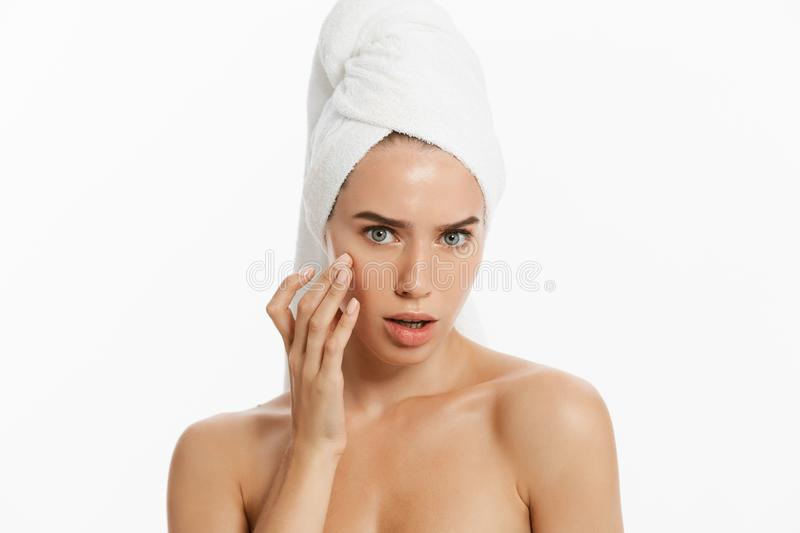 Close up beauty portrait of a smiling beautiful half naked woman applying face cream isolated over white background. royalty free stock photography
