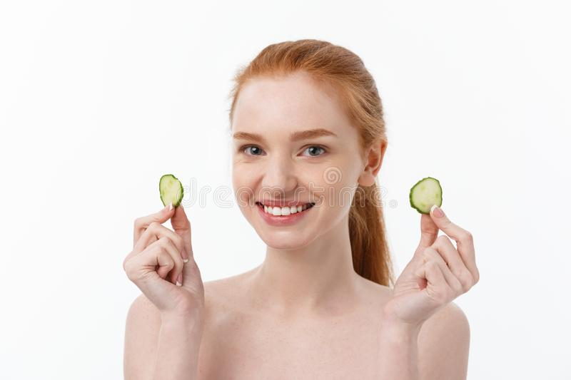 Close up beauty portrait of a smiling beautiful half naked woman holding cucumber slices at her face isolated over white. Background stock photos