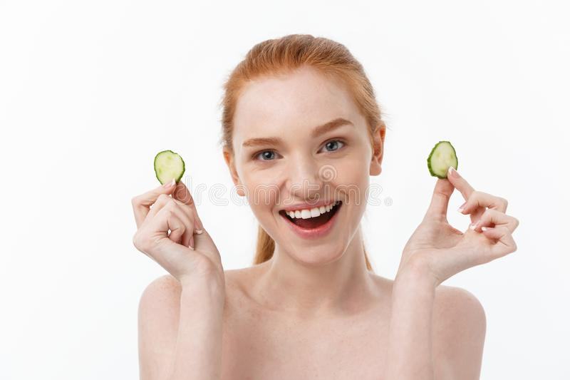 Close up beauty portrait of a smiling beautiful half naked woman holding cucumber slices at her face isolated over white. Background royalty free stock image