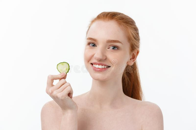 Close up beauty portrait of a smiling beautiful half naked woman holding cucumber slices at her face isolated over white. Background stock photography