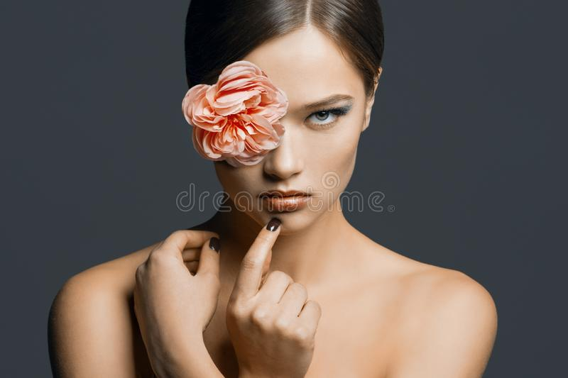 Close-up beauty portrait of young beautiful woman with health skin, with flower on her face, bare shoulders. Gray studio stock photography