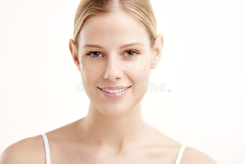 Close-up beauty portrait of a beautiful young woman with eye mask under her eye stock photography