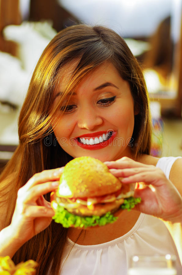 Close up of a beauty smiling woman in cafe holding a delicious hamburger.  royalty free stock photo