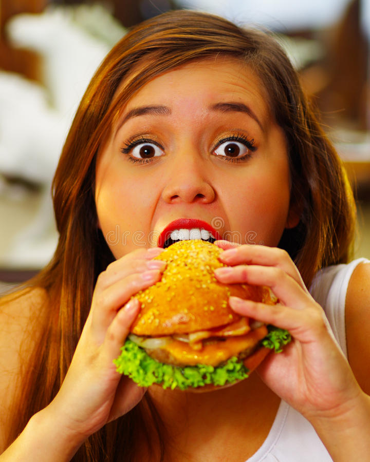 Close up of a beauty woman in cafe eating a delicious hamburger.  royalty free stock photo