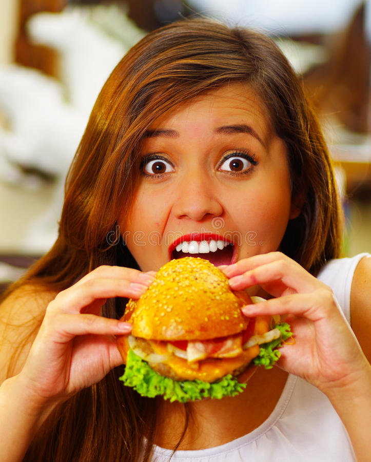 Close up of a beauty woman in cafe eating a delicious hamburger.  royalty free stock photography