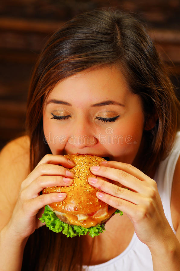 Close up of a beauty woman in cafe eating a delicious hamburger.  stock images