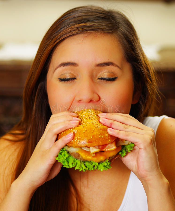Close up of a beauty woman in cafe eating a delicious hamburger.  stock photo