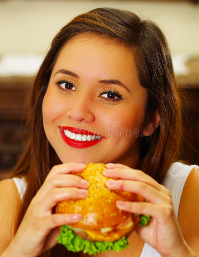 Close up of a beauty woman in cafe holding a delicious hamburger.  stock photos