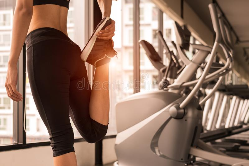 Close up beauty woman stretching legs in workout fitness gym center with sport equipment and treadmill background. Sporty girl wa royalty free stock photo