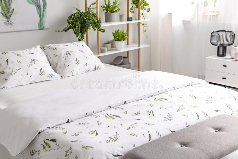 Close-up of a bed dressed in organic cotton green plants pattern white linen in a sunny bedroom interior. Real photo. Concept royalty free stock photos