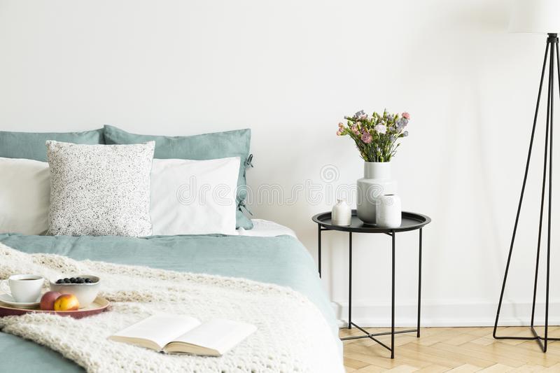 Close-up of a bed with pale sage green and white linen, pillows and a blanket in a sunny bedroom interior. A round black metal sid stock image