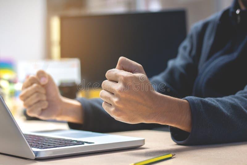 Close-up Bedrijfsmens die met opgeheven vuisten bij haar bureau zitten Cel stock afbeelding