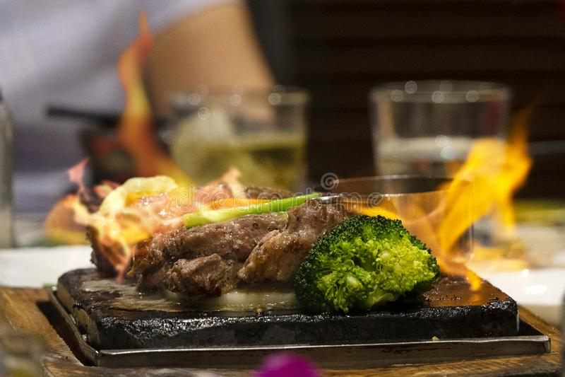Close up beef on hot dish on fire with vegetables. Live cooking in the restaurant royalty free stock photos