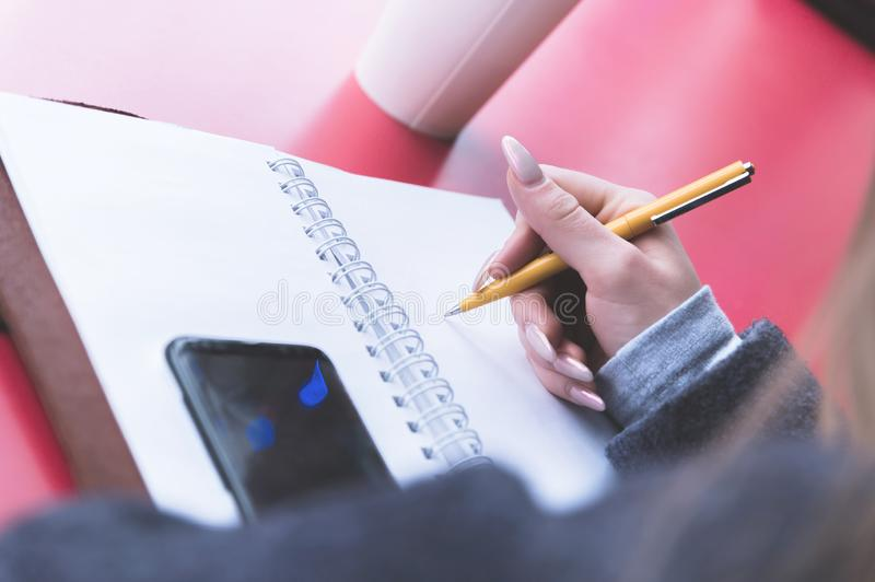 Close-up from behind the back of a young woman in a winter polto is holding a ballpoint pen and is going to write royalty free stock image