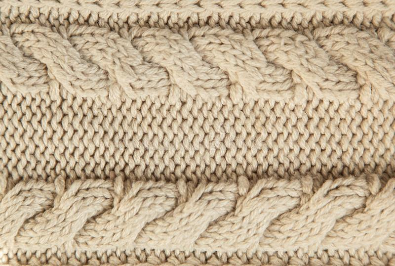 Close up of beige knitted winter sweater with pattern as textured material concept. stock images