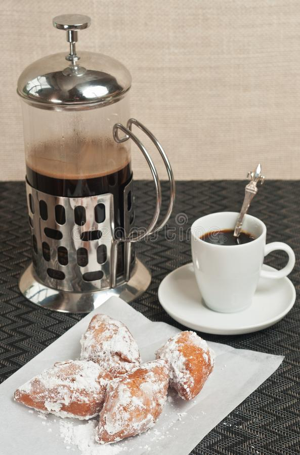 Close up of beignet fritters and french coffee press. Top view, close up of four freshly baked, homemade, beignet fritters on a white paper napkin with a cup of stock photo