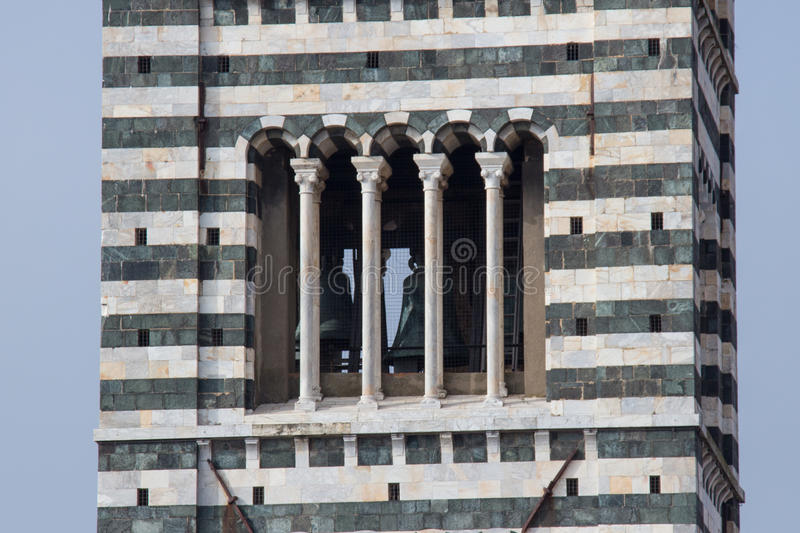 Close up of Bell tower of Duomo di Siena. The view of Romanesque stylistic patterns on Campanile. Tuscany, Italy. stock photography