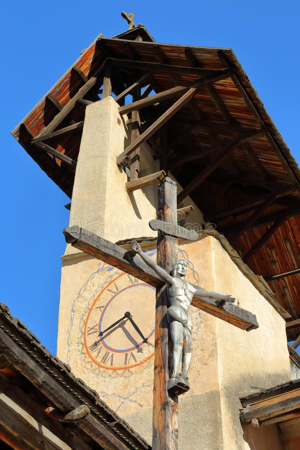 Close-up on the bell tower of Saint Sebastien Church and the Cross of Jesus Christ, Ceillac royalty free stock image