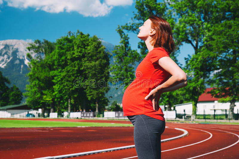 Close-up belly of pregnant woman on sport stadium. Pregnant sporty fitness woman suffering lower back pain on sport stadium. Concept of training, workout stock image