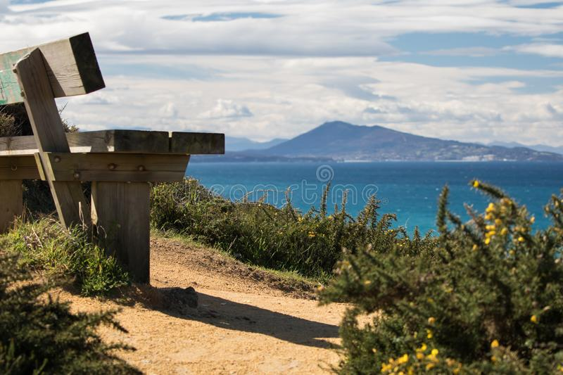 Close up on bench on coastal footpath cliff, relaxation concept, admiring scenic aerial view on atlantic coastline, bidart, france royalty free stock photos