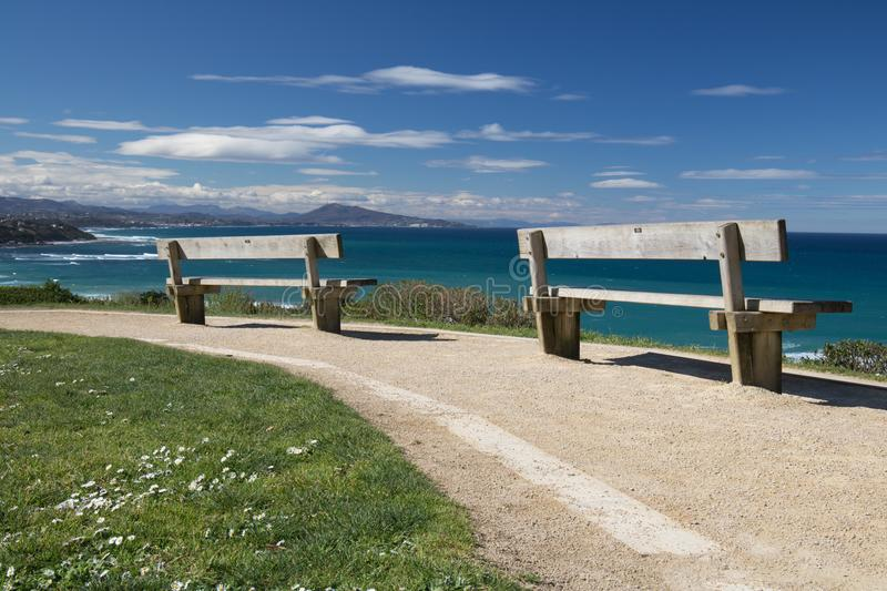 Close up on benches on coastal footpath cliff, relaxation concept, admiring scenic aerial view on atlantic coastline, bidart, fran. Ce stock image