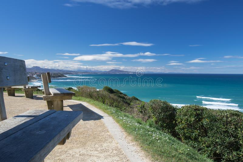 Close up on benches on coastal footpath cliff, relaxation concept, admiring scenic aerial view on atlantic coastline, bidart, fran. Ce royalty free stock photography