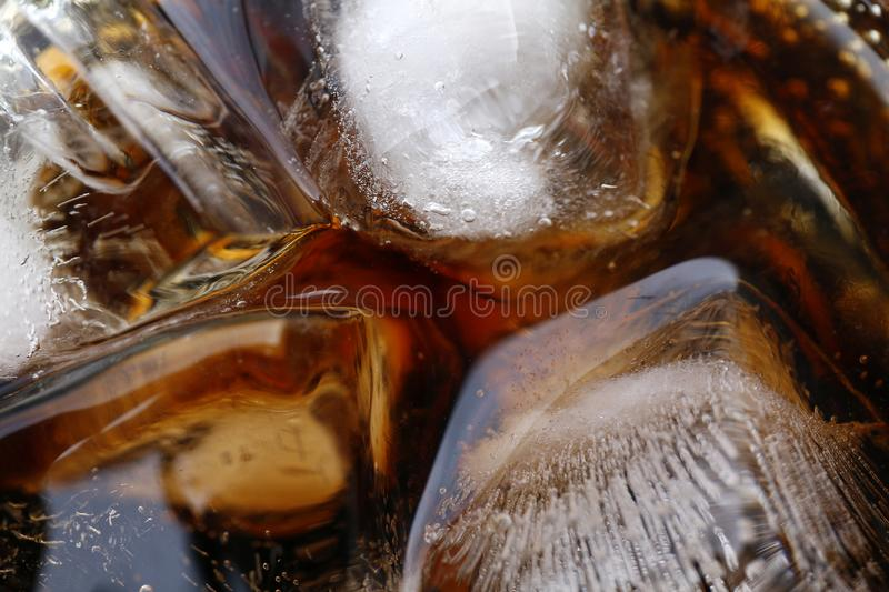 Close-up beverage cola and cubes ice refreshing cool in glass, black cola soda in glass with ice cubes for refreshments feel royalty free stock images