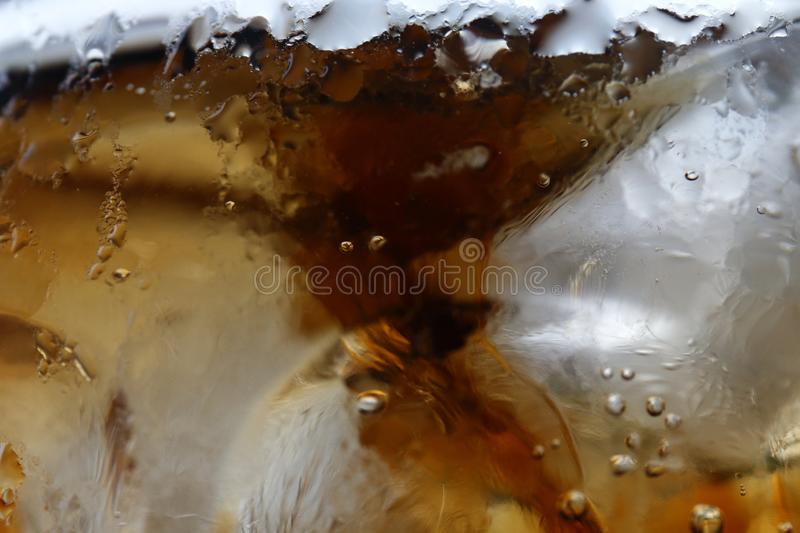 Close-up beverage cola and cubes ice refreshing cool in glass, black cola soda in glass with ice cubes for refreshments feel stock photos