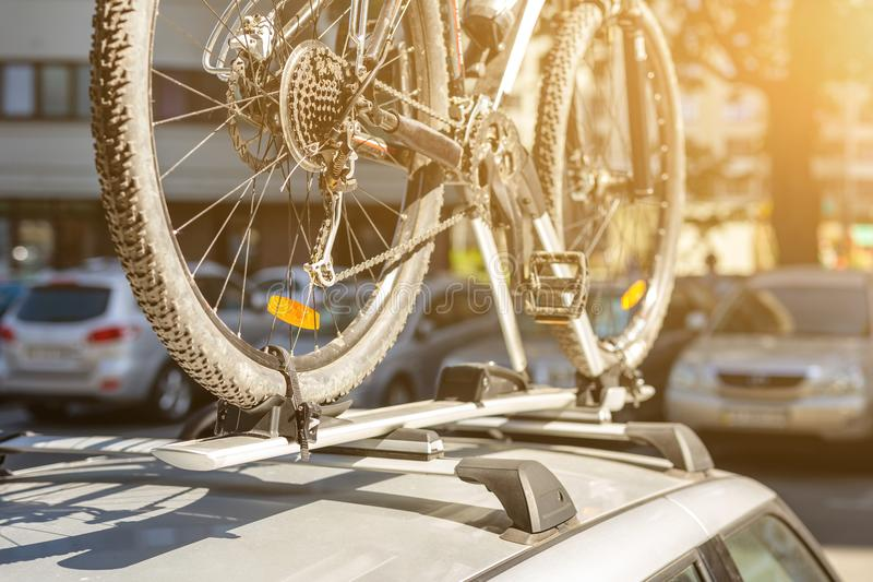 Close-up bicycle on car roof rack railing at outdoor parking. Vehicle with mounted bike on rooftop. Active sport touristic trip co stock photos