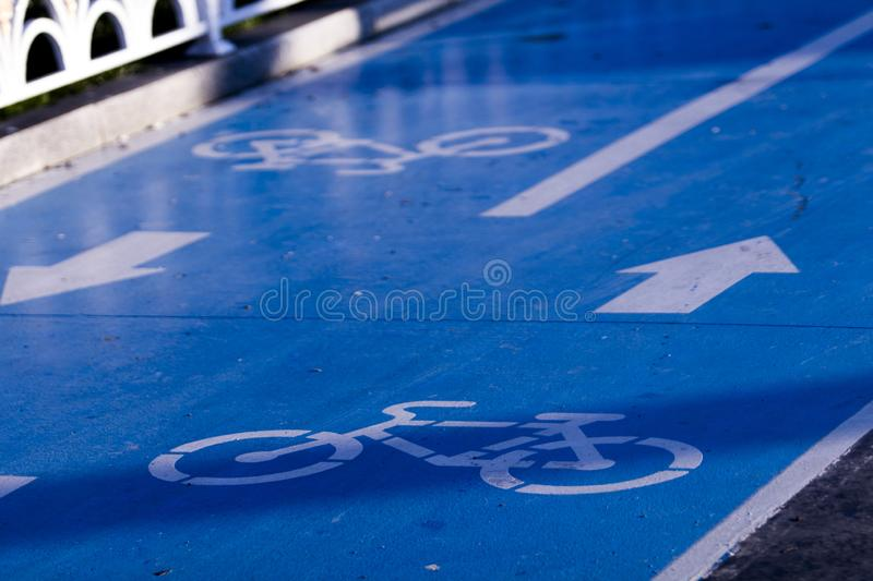 Close-up of a bicycle route sign in two directions with blue ground cover material, arrows and icons. Bicycles have enabled expansion of cities in the 19th stock image