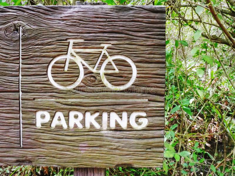 Bicycle Symbol and Parking Text on Wooden Textured Sign Board royalty free stock images