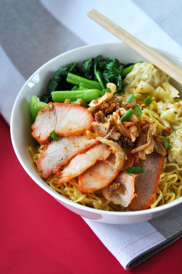 Close up Big Bowl of Egg Noodles with Grilled Pork and Wonton royalty free stock photography
