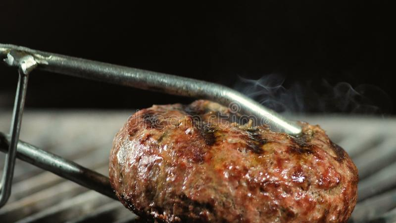 Close up of big juicy burger patty being grilled, iron tongs turning over the patty to the other side for final cooking.  stock photo