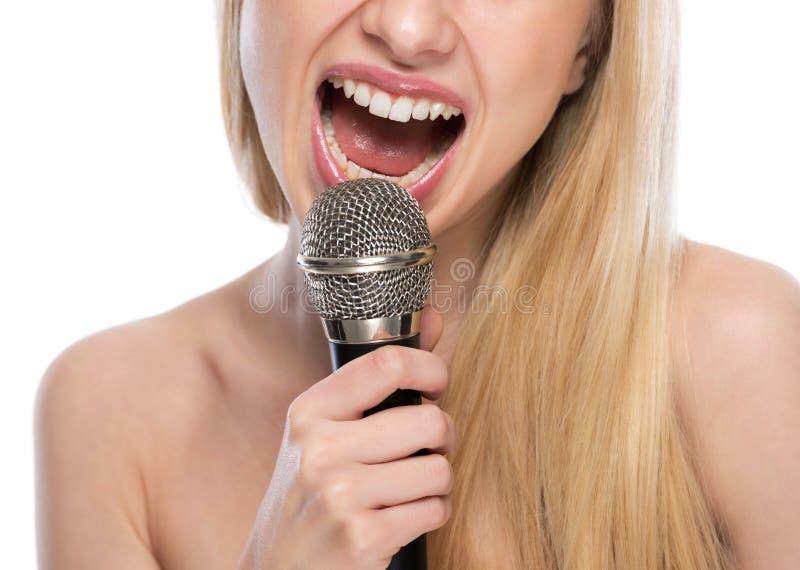 Close-up bij het jonge vrouw zingen met microfoon stock fotografie