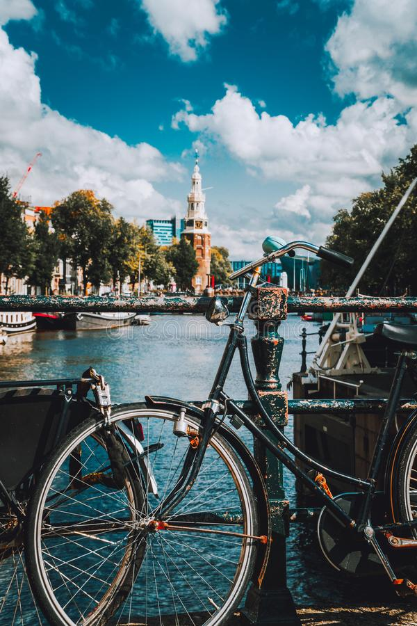 Close-up of Bike parked on a bridge in Amsterdam, Netherlands. Typical cityscape with Amstel river and motion clouds at the royalty free stock photos